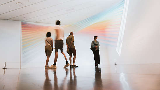 People walking through a gallery space and looking at a rainbow coloured light installation