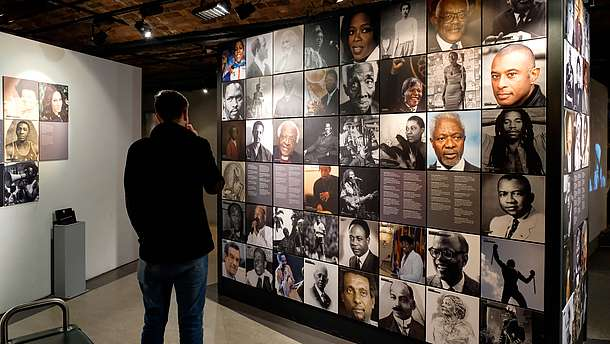 A person with their back to the camera is looking at photo collage that is covering a wall.