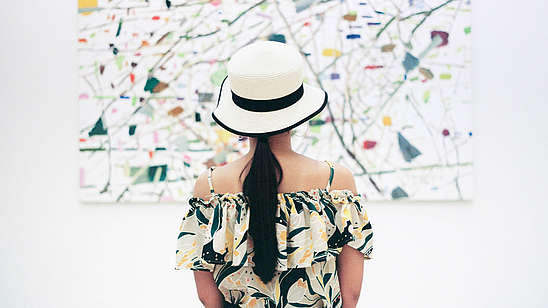 A woman wearing a hat is standing with her back to us. She is in centre of the picture and of the painting in front of her.