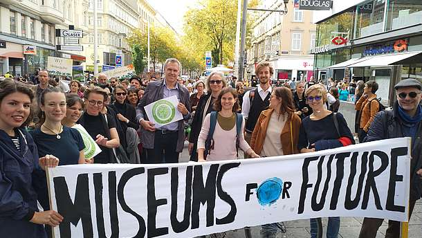 "Group of people at a demonstration for the environment carrying a banner that says ""Museums for Future"""