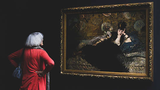Woman with her back to the camera is looking at a painting of a person in a black dress. The wall is also black which contrasts the woman's red dress.