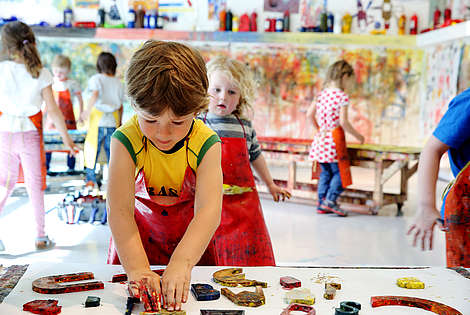 a boy in front is painting in a workshop  © ZOOM Kindermuseum, Image: J.J. Kucek