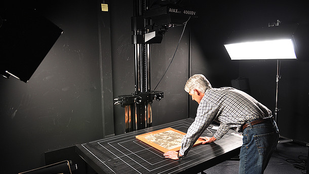Man leaning over a table positioning a picture that he is photographing in order to digitalize it  © Image: Andy Colwell