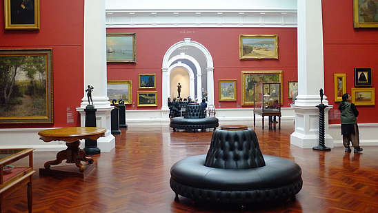 Photo from inside a museum hall with red walls.