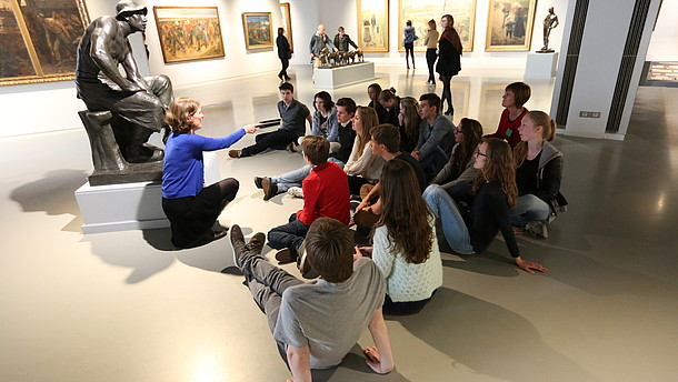 Group of people are sitting down by a statue in a gallery and listen to a person.  © Image: J. Pierrard