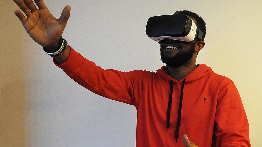 Man in an orange hoodie is using a pair of virtual reality glasses  © Image: Hammer Tusk