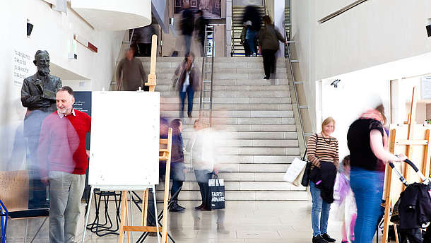 Several people moving in a staircase during a painting workshop at a museum.