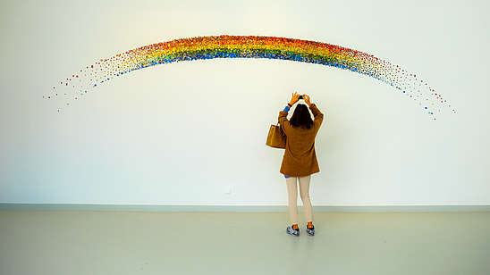 A person reaches up to take a photo with their phone of a rainbow that is painted on a wall.