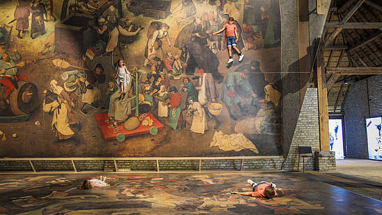 Two kids lay down on a blown up version of a Bruegel painting. A huge tilted mirror shows them as part of the painting.