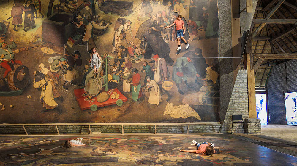 Two kids lay down on a blown up version of a Bruegel painting. A huge tilted mirror shows them as part of the painting.  © Bokrijk