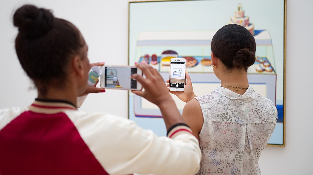One person is taking picture of another person who is taking a picture of a painting.  © Image: Christian Fregnan