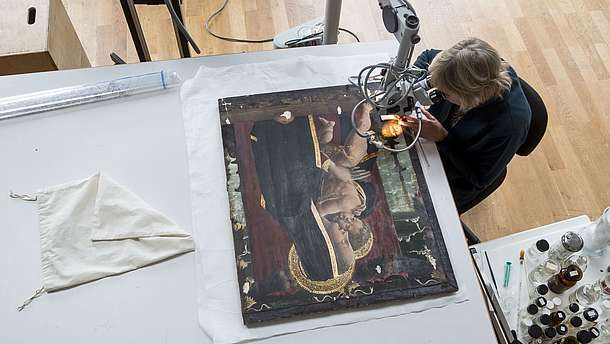 Bird perspective of someone doing restoration work on an icon painting.