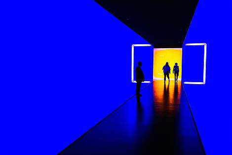 Three people walk through a light instillation from a room lit in yellow into a blue tunnel   © Image: Werner du Plessis