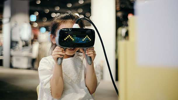 A girl is using a pair of VR goggles in a gallery space. The child is smiling and the goggles mirror the smile with happy eyes animation.
