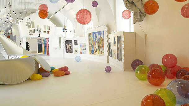 Empty spacious and white room filled with plastic see-through balls. The balls are scattered around the room on the floor, on the walls and attached to the ceiling.   © ZOOM Kindermuseum, Image: Alexandra Eizinger