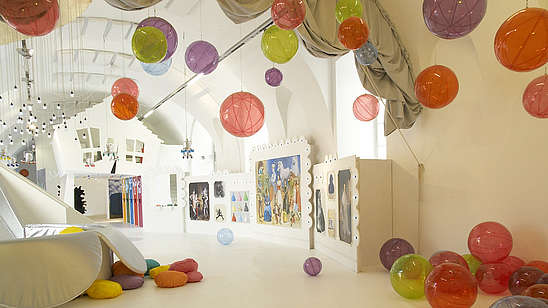 Empty spacious and white room filled with plastic see-through balls. The balls are scattered around the room on the floor, on the walls and attached to the ceiling.