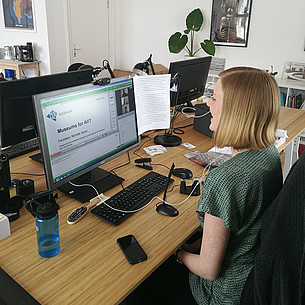 Person sitting in front of a computer preparing a webinar.