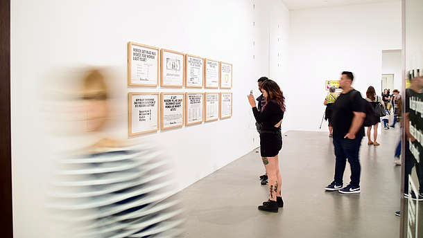 People are taking photos and look at paintings inside a gallery. A person in the foreground is leaving the room and is therefore blurry in the picture.