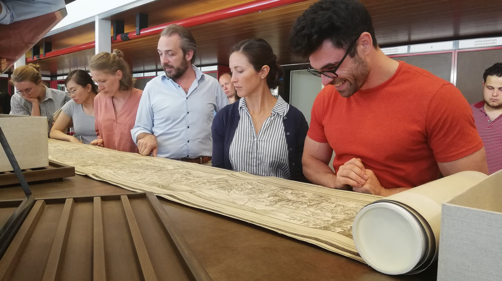 Five people reading an ancient text that is rolled out in front of them.  © Flemish Art Collection-SummerCourse 2019