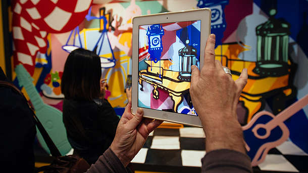 Person takes a photo of a colourful and abstract installation using a tablet