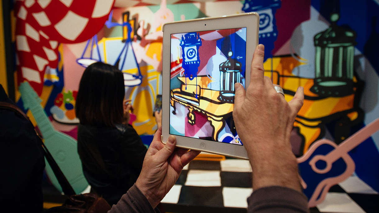 © Image: Courtesy Pimlico Project Person takes a photo of a colourful and abstract installation using a tablet