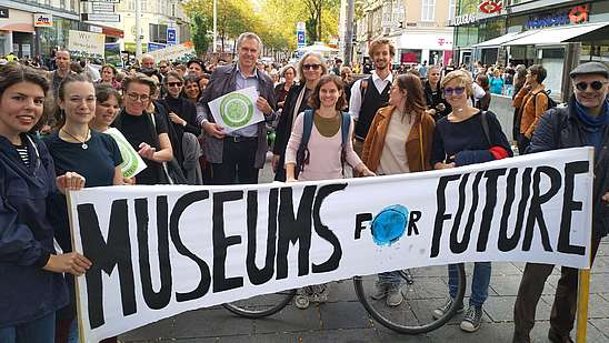 """Group of people at a demonstration for the environment carrying a banner that says """"Museums for Future"""""""