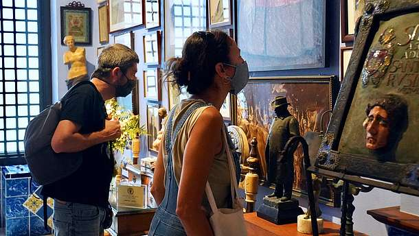 Two people wearing nose and mouth covering masks are looking at art hanging on the wall.