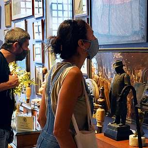 © Arxiu Fotogràfic del Consorci del Patrimoni de Sitges Two people wearing nose and mouth covering masks are looking at art hanging on the wall.