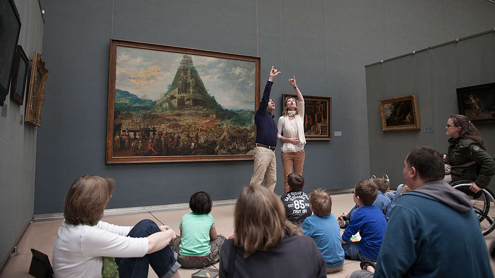 Two guides make a big gesture together to explain a painting to a group of people.  © MRBAB