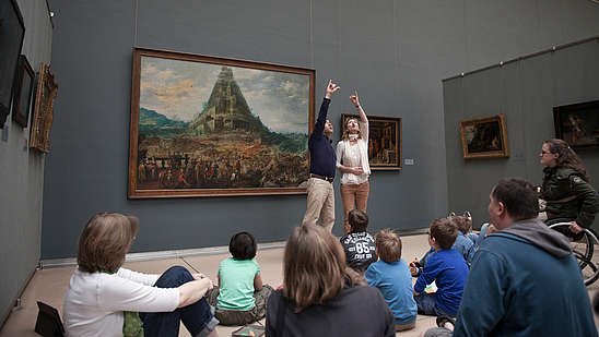Two guides make a big gesture together to explain a painting to a group of people.