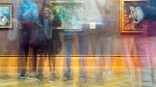 The photographer has used the slow shutter function so that it looks like several people are moving quickly in front of a wall with three pictures on it.