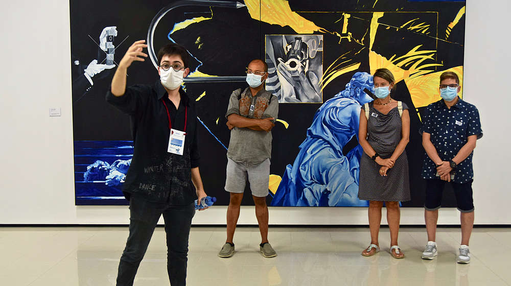A man is taking a selfie of himself and three other people standing behind him in front of a big painting. They are all wearing face and mouth covering masks.   © Arxiu Fotogràfic del Consorci del Patrimoni de Sitges
