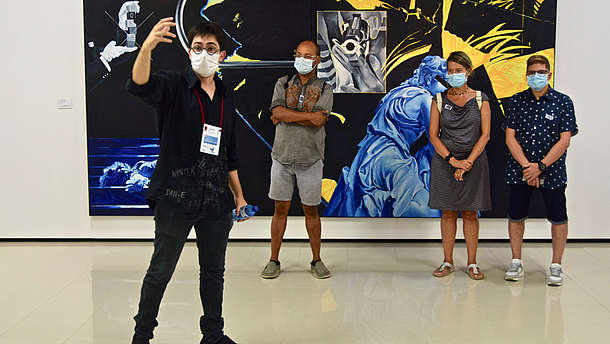 A man is taking a selfie of himself and three other people standing behind him in front of a big painting. They are all wearing face and mouth covering masks.
