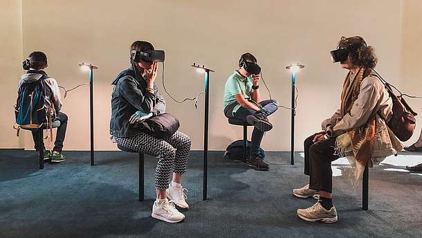 Four people are sitting in a gallery space. All four are wearing goggles and headphones and they are experiencing some kind of virtual reality art.