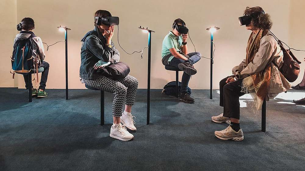 Four people are sitting in a gallery space. All four are wearing goggles and headphones and they are experiencing some kind of virtual reality art.  © Image: Lucrezia Carnelos