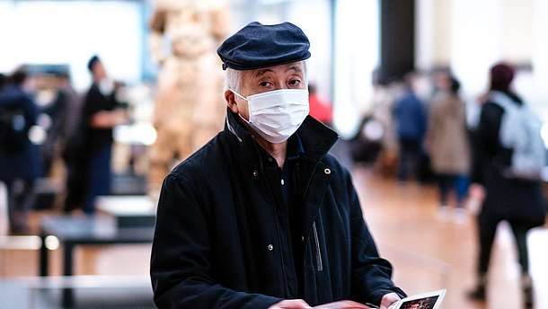 Man wearing moth and nose mask is walking through an exhibition space while flipping through pamphlet.