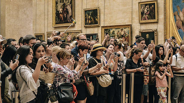 Big group of tourists stand behind a barrier rope and take a photo of an art piece that is out of view  © Image: Alicia Steels