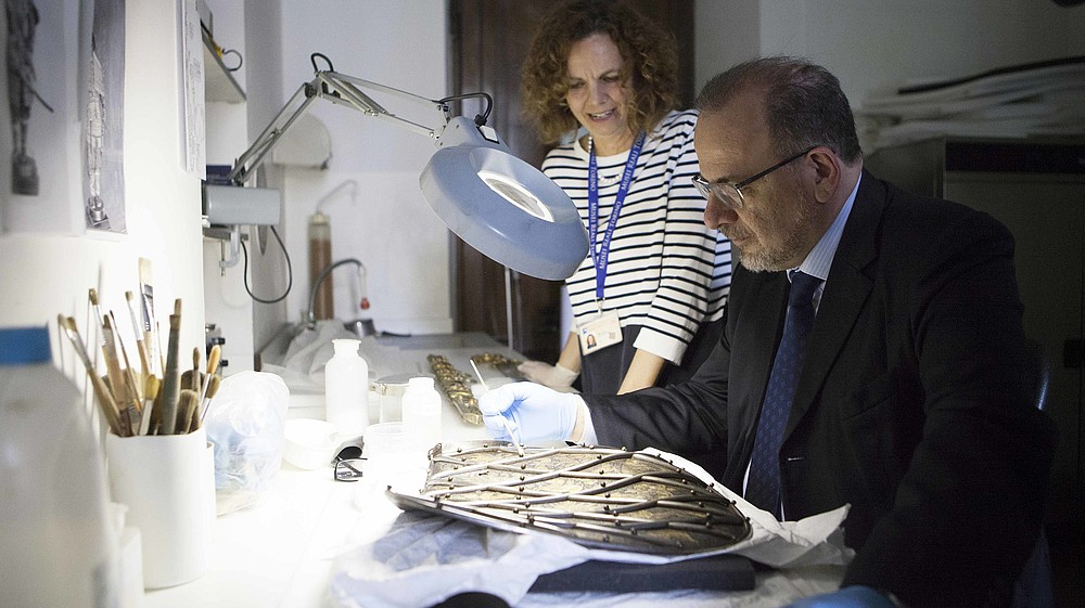 Man restoring an ancient piece of art with the guidance of a restaurator Luca Jahier, president of the European Economic and Social Committee at the Royal Museums, Turin © Image: Daniele Bottallo