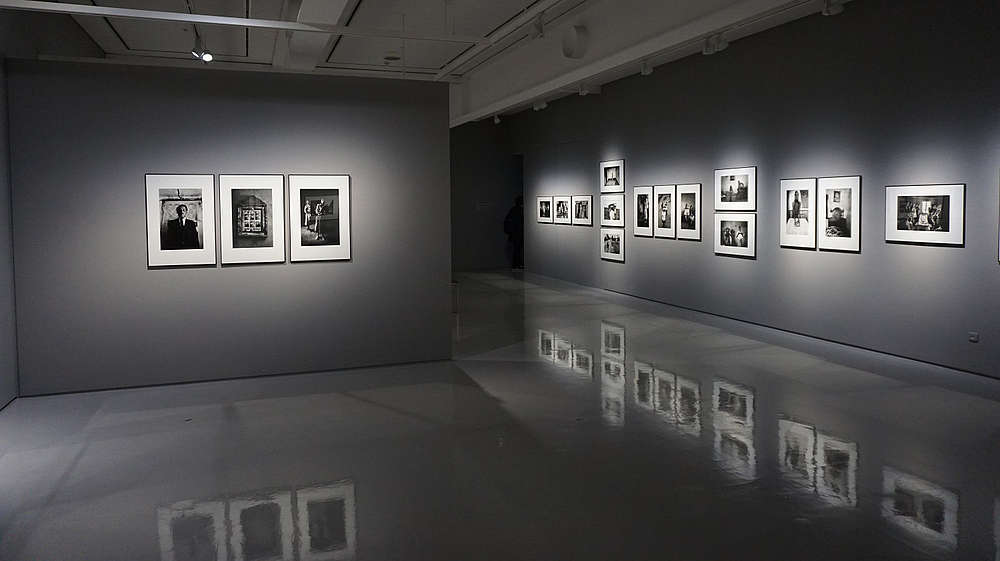 Grey gallery space with shiny floors that reflects the photos hung on the walls.  © Image: Eric Park