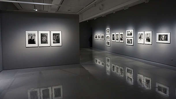 Grey gallery space with shiny floors that reflects the photos hung on the walls.