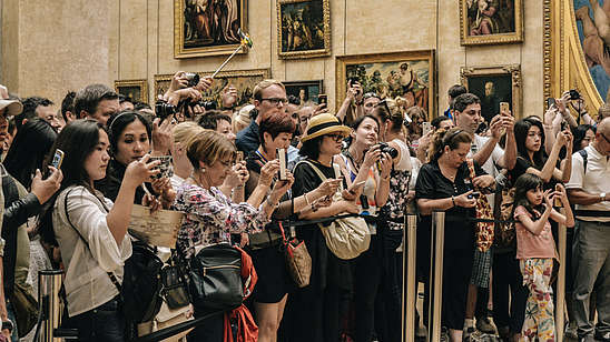 A large group of tourists stand behind a rope fence inside a museum to take photos of something outside of the picture.