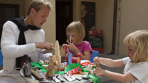A man helps two children build paper dolls.