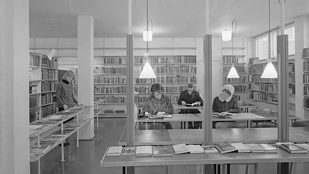 Black and white photo showing four people browsing or reading books in a book shop or library..