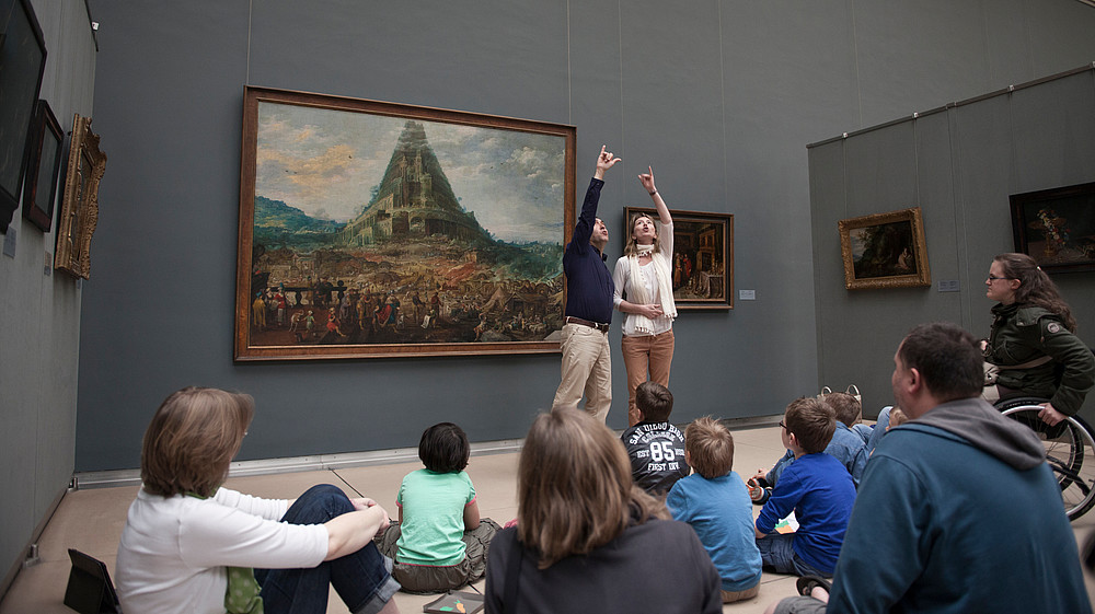 Two guides using sign language to explain a painting in front of a group of people   © MRBAB