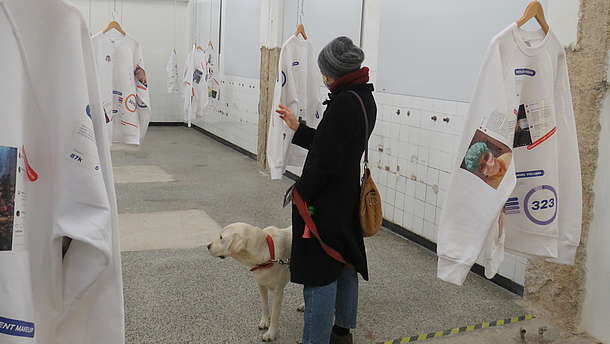 Person wearing a mouth and nose mask is standing in a gallery together with her dog. She is looking at one of many exhibited sweatshirts that are hanging from the ceiling.